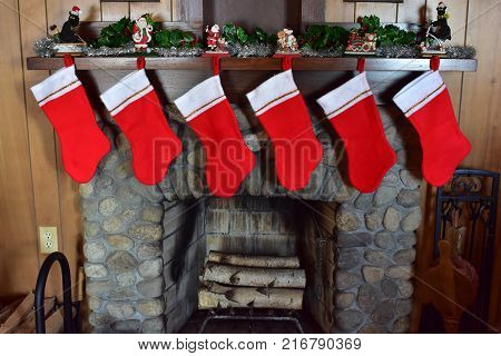 6 Christmas stockings hanging on stone fireplace with no names and not stuffed