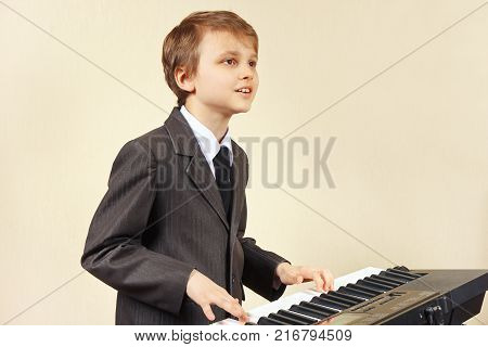 Young beginner pianist in a suit play the keys of the electronic synth