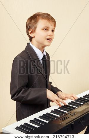 Young beginner musician in a suit playing the electronic synthesizer