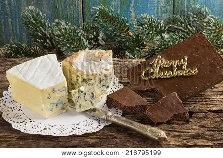 Cambozola Bleu d'auvergne noble gourmet cheeses with blue and white mold and bitter dark chocolate on wooden background branches pine needles.Christmas card.Merry Christmas