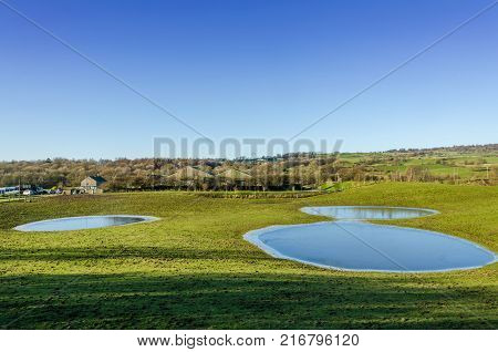 Frozen flooded fields on an English farm in Winter with woodland in the background