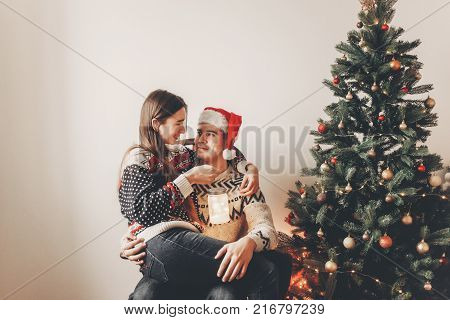 Merry Christmas And Happy New Year Concept. Stylish Hipster Couple Exchanging Gifts In Festive Room