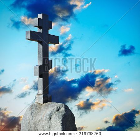 stone cross on a pedestal against the dawn sky