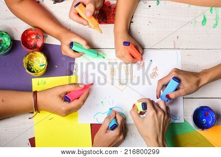 Artists wooden table with paints and colored paper. Hands hold colorful markers and draw top view. Markers in male and female hands draw on white paper with cute drawings. Art and idea concept