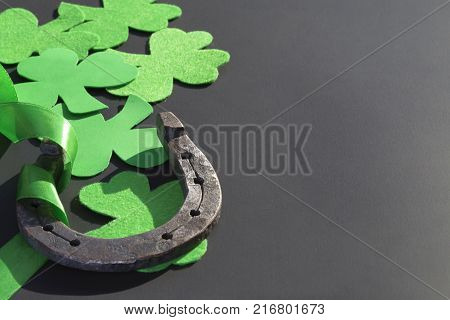 Template preparation for St. Patrick's Day. Clover and horseshoe on a dark background with place for text. Symbols of luck and fortune on isolation with copy space. Trefoil and rusty horseshoe.