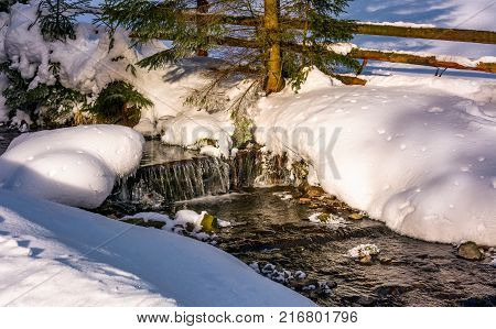 Brook With Cascades In Winter Forest