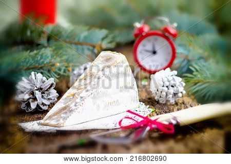 Clock alarm clock red cheese brie pine branches cones Cutlery fork knife on wooden background Concept of Christmas and New year Selective focus Tinted