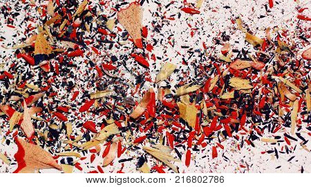Colorful pencil shavings on white background. Blue and red crayon shavings close-up.