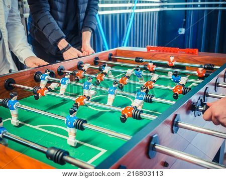 Cropped image of active people playing foosball. table soccer plaers. Friends play together table football.