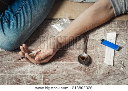 Hand addict and syringe with heroin lying on the floor. The concept of anti drugs. male drug addict hand drugs narcotic syringe. poster