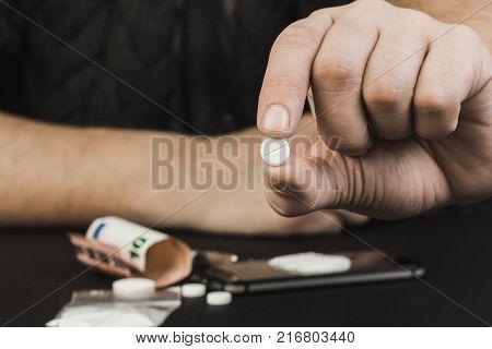 A drug addict or a drug dealer holding a pill with the drug.