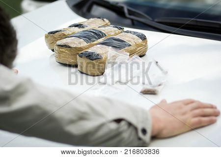 Detained Criminal On The Hood Of A Car With Packets Of Drugs.
