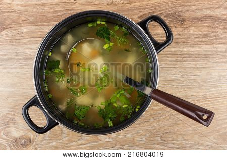 Soup with chicken meat and vegetables in black pan ladle on wooden table. Top view