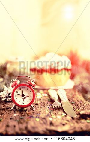 Red alarm clock on wooden background with green branches of pine cones and Cutlery. On the clock 11:45 - it's eleven forty five.Vintage tinted glass.The concept of the Christmas and New Year