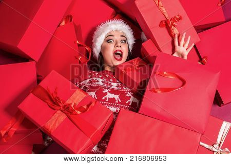 Funny young woman in a New Year's dress lying on a mountain of gifts. Christmas sale. Emotional brunette in Santa hat
