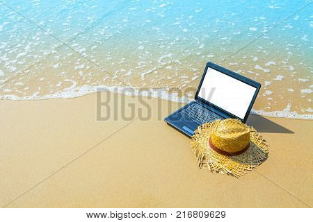 laptop or computer notebook on sea beach and wave - business travel background with empty white screen clipping path