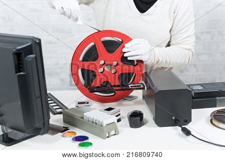 a technician with white gloves digitalizing a 16mm film
