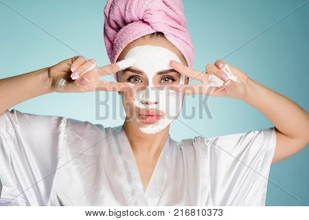 an attractive girl with a pink towel on her head applied a white nutritious mask to her face