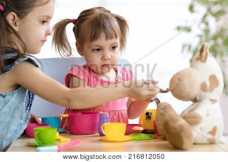Close-up portrait of cute adorable little kids feeding caw soft plush toy poster