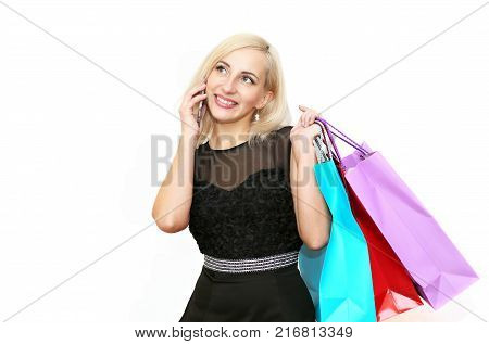 Happy young girl enjoying shopping after shopping and talking on the phone with a smile isolated on white background.Happy young girl enjoying shopping after shopping and talking on the phone with a smile isolated on white background.