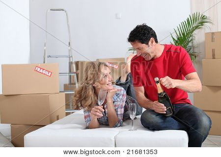 Couple lying on an unmade sofa bed celebrating their new home with champagne