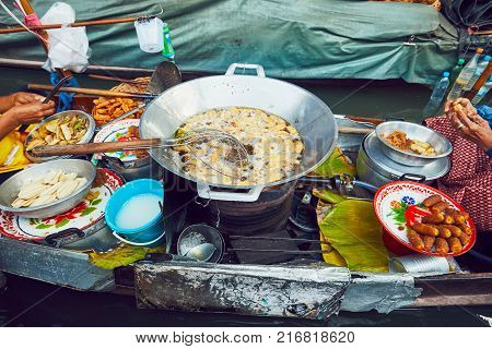 Cuisine on the boat. Preparation of fried bananas. Traditional old floating market Damnoen Saduak in Ratchaburi near Bangkok Thailand.