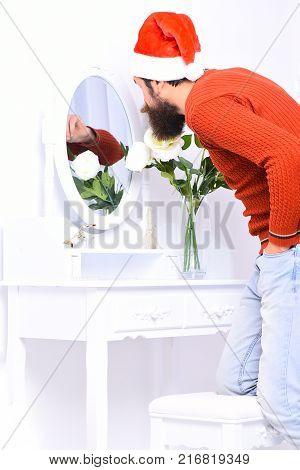 Santa Claus Looks Into Mirror. Guy Leans Down To Mirror