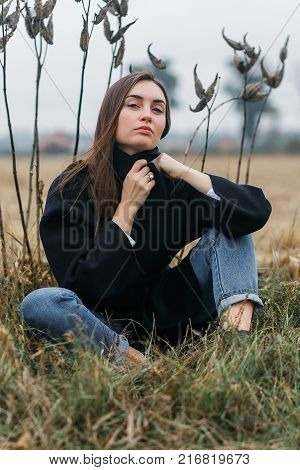 sad young woman sitting in long dry autumn grass seeking for solitude and peaceful silence from the city, cloudy weather.
