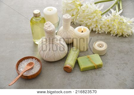 Spa setting with candle, soap ,love flower, herbal, ball on gray background