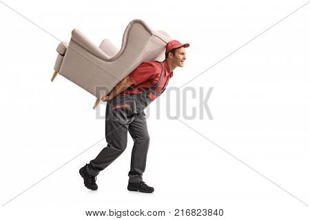 Full length profile shot of a mover walking and carrying an armchair on his back isolated on white background