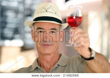 old man raising a glass of claret