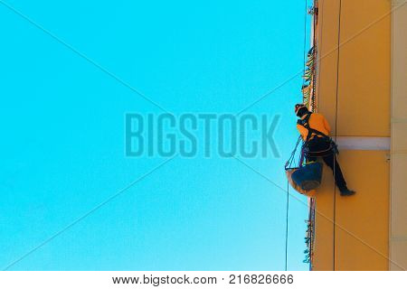 Construction and renovation background. Worker climbing on the wall. Man working at height