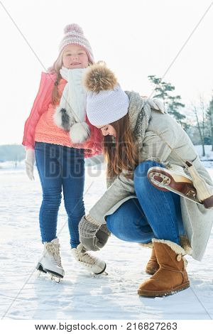 Mother bind shoes from daughter before ice-skating