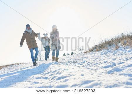 Happy family takes a walk in the snow in winter