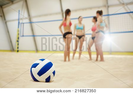 Volley ball on sand field on background of four young participants having break