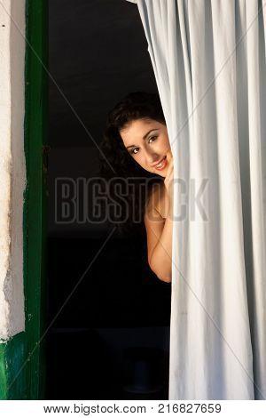 Happy woman hiding behind a door curtain of a derelict house