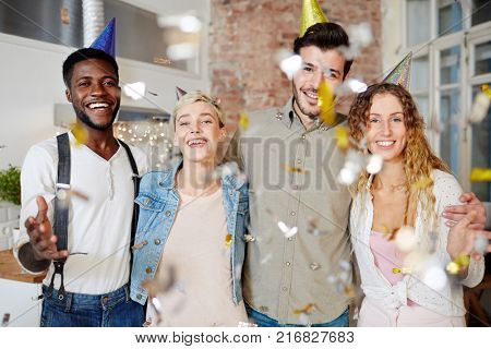 Young affectionate friends in birthday caps having fun at party
