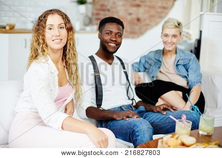 Young intercultural people relaxing at home in living-room after working day