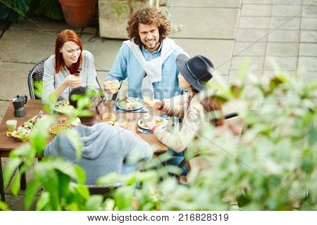 Young companions having talk during dinner by served table outdoors