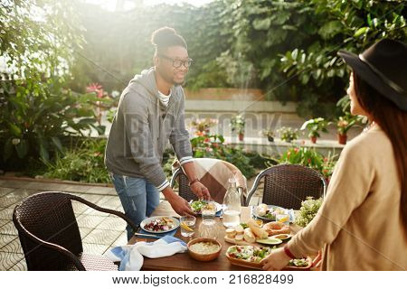 Two young intercultural friends choosing places by served table and preparing to meet guests