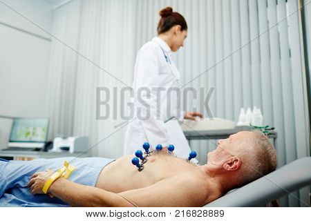 Senior patient having his heart examined with new cardiological equipment in modern clinics