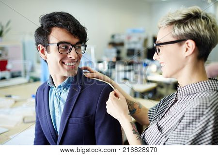 Young businessman talking to his tailor during alterations in workshop