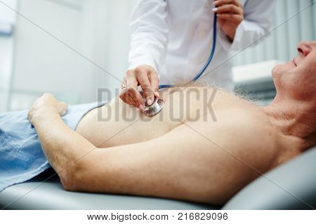 Doctor listening to heartbeat of senior patient with stethoscope