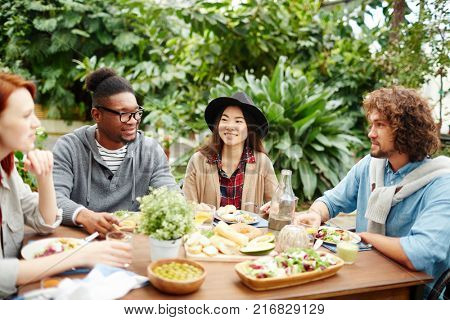 Group of young intercultural friends having talk by served table at breakfast
