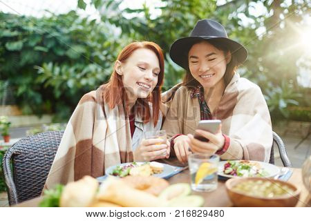 Intercultural girls watching something curious in smartphone or talking through video-chat by table