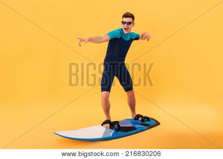 Image of happy surfer in wetsuit and sunglasses using surfboard like on wave over yellow background