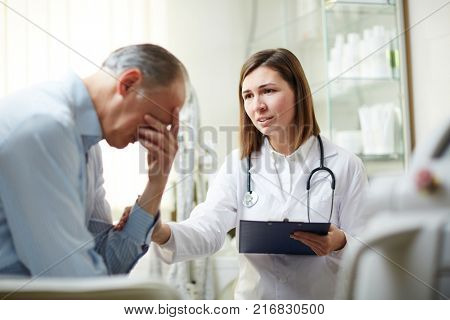 Young therapeutist comforting upset mature patient during appointment in hospital