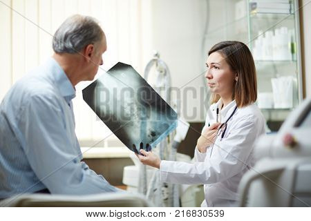 Young radiologist showing x-ray image to her aged patient and giving recommendations about treatment