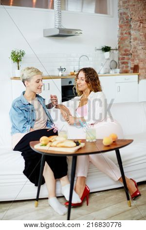 Friendly girls sitting on sofa by small table with snack and having talk