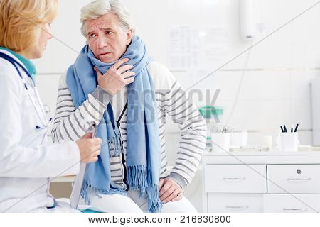 Sick senior man with scarf around neck complaining his doctor about symptoms of flu